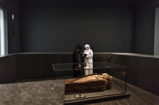 ABU DHABI, UNITED ARAB EMIRATES-November 13, 2017: Visitors to the Louvre Abu Dhabi look at the Sarcophagus of Henuttawy: coffins and mummy's wrapping. Egyptian civilisation Egypt, 950-900 BCE. Painted wood, stuccoed and painted cloth. In the First Great Powers Gallery. Louvre Abu Dhabi CREDIT: Katarina Premfors/The New York Times